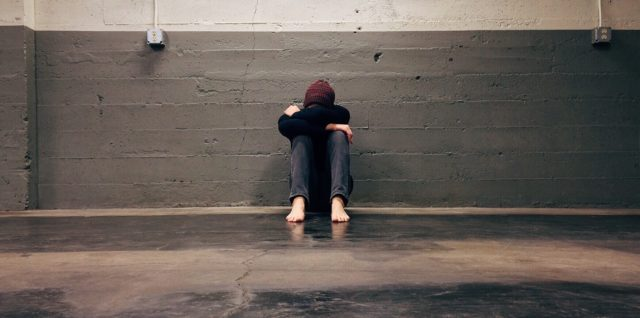 An individual sits head in hands up against a wall, seemingly overcome with emotion.