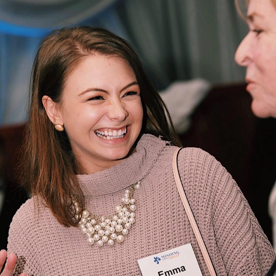 Emma Barrera grins at another individual at a mental health seminar.